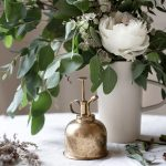 white flowers on desk with bronze bell