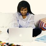 Woman on bed creating content with laptop