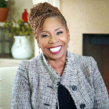 Iyanla Vazant sits on chair and smiles
